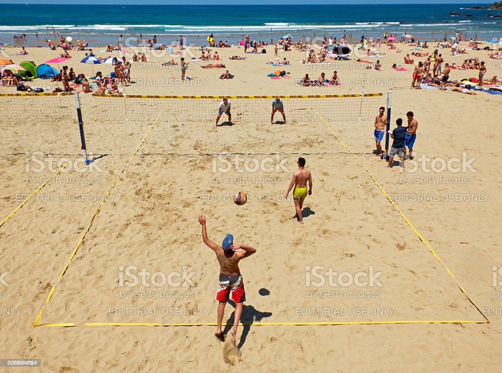 Young men playing volleyball in Zurriola beach, San Sebastian. Spain. stock photo