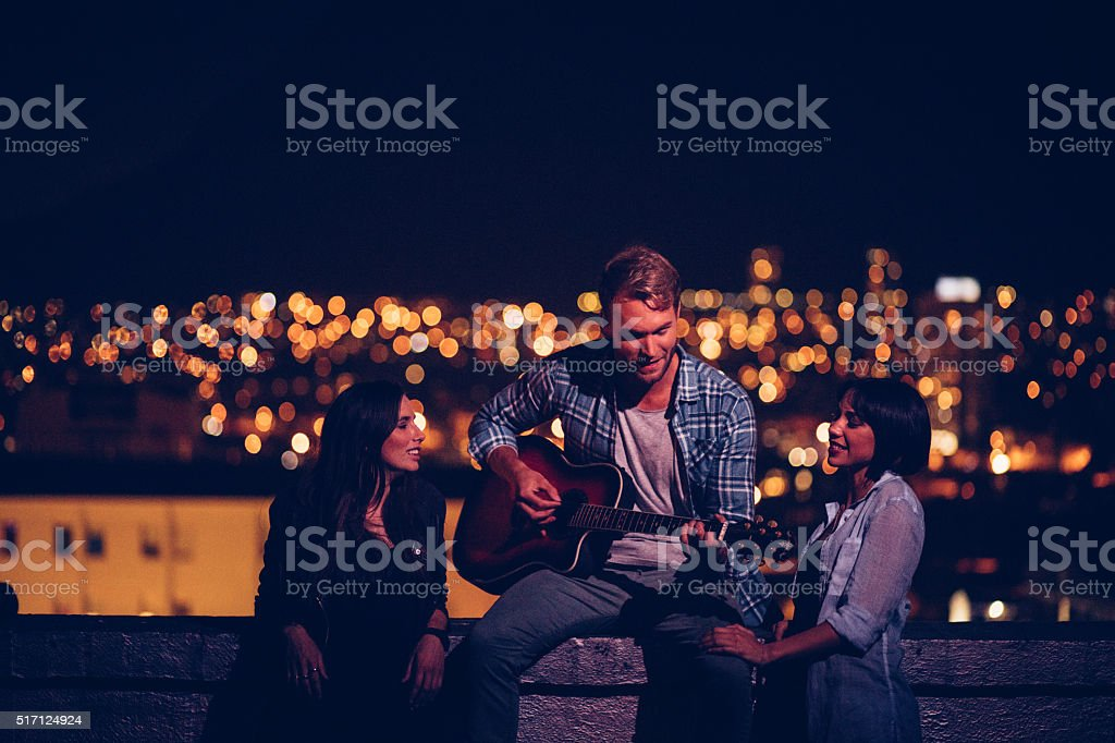 Young men plays guitar for his two friends on rooftop stock photo