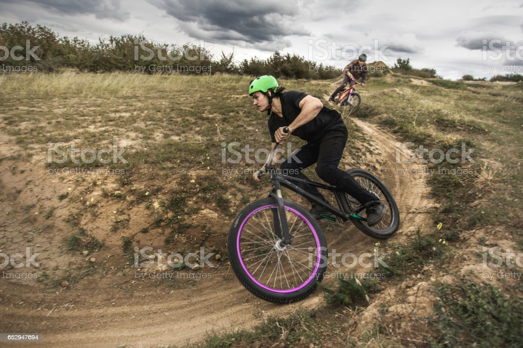 Young men racing with mountain bikes on dirt road. stock photo