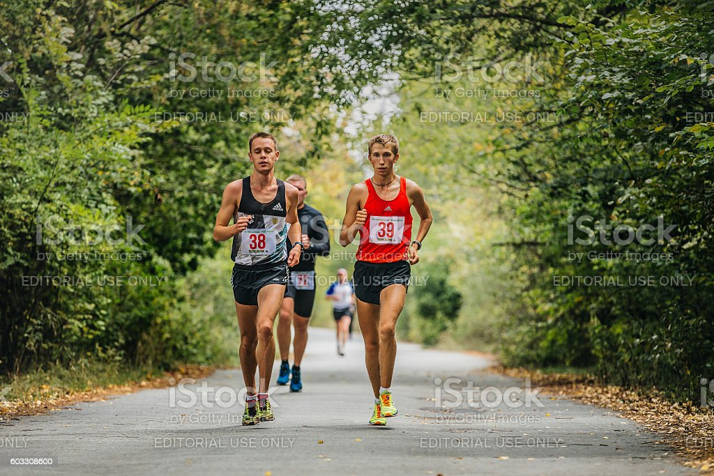 young men runners synchronous run in autumn Park royalty-free 스톡 사진