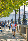 Young men running  by the River Thames embankment