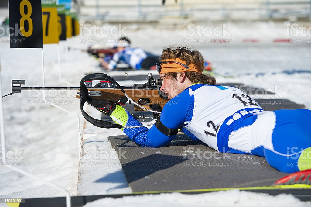 Young men shooting during biathlon competition stock photo