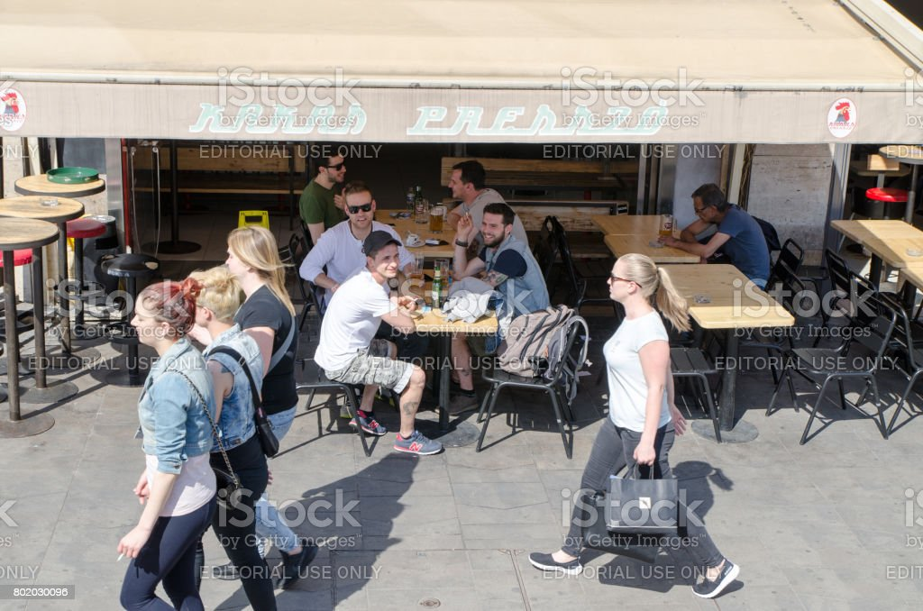 Young men sitting at estaurant patio in Budapest during summer day and looking at girls passing by stock photo