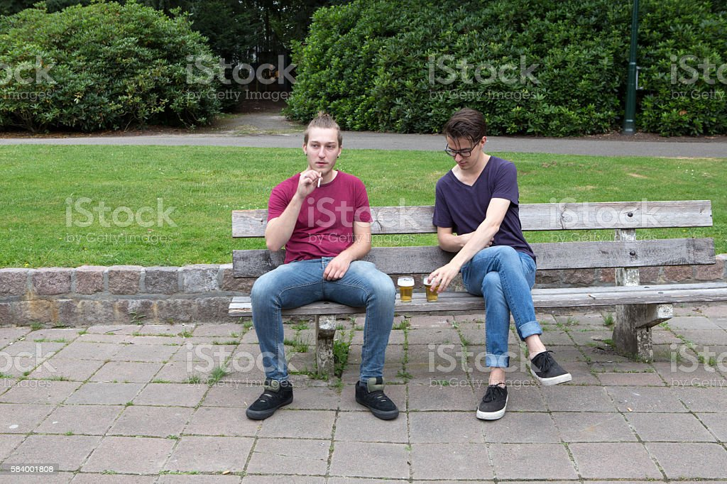 young men smoking and drinking alcohol stock photo