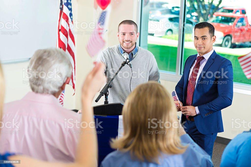 Young men talking at podium during city council meeting stock photo