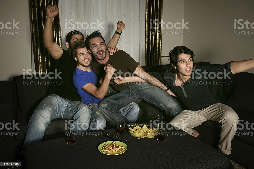 young men watching sports competition stock photo