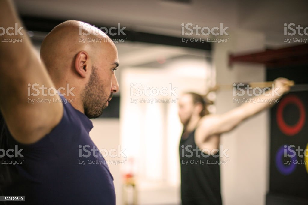 Young men workout in gym. Men stretching hands in gym. stock photo