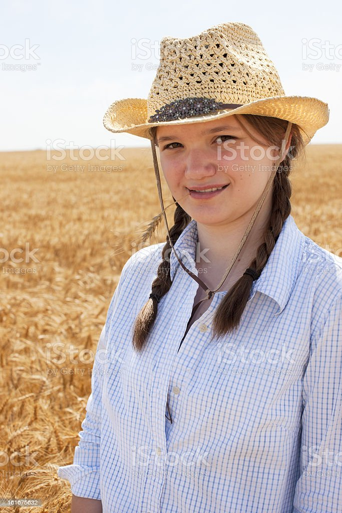 Young Midwestern  Cowgirl Stands in Wheat Field on Farm stock photo