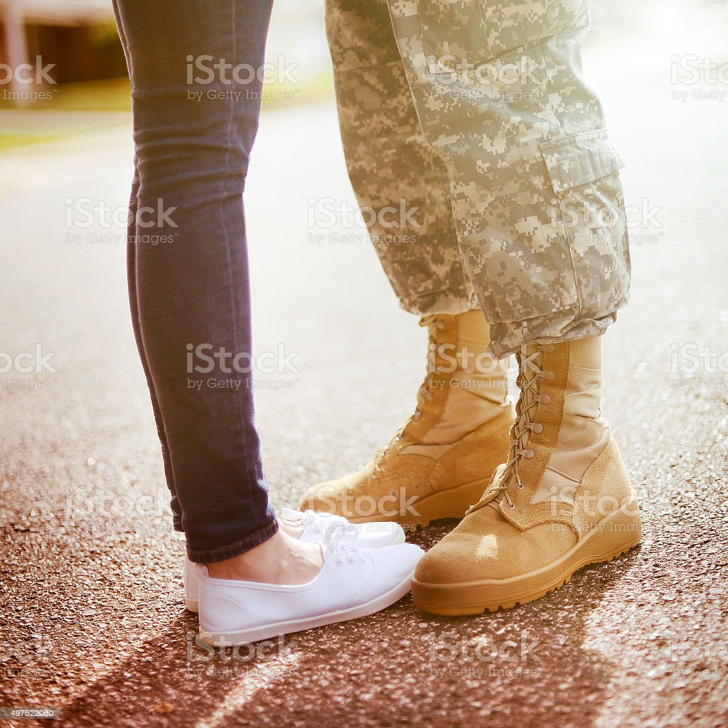 Young military couple kissing each other, homecoming concept stock photo