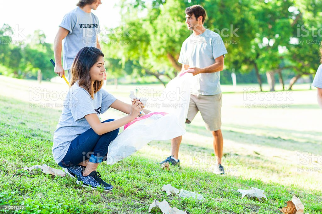 Young millenial volunteers pick up trash in park stock photo