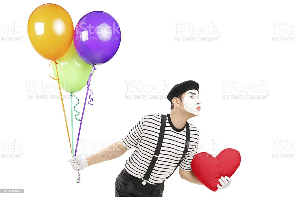 Young mime artist with balloons and red heart giving kisses stock photo