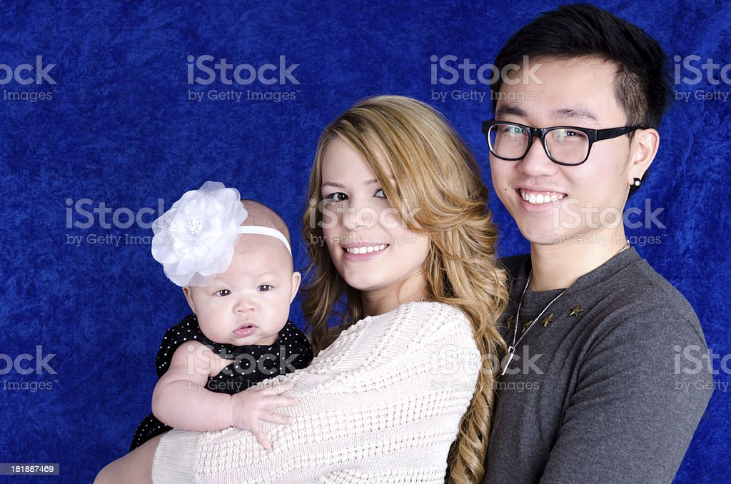 Young mixed race couple with daughter on blue. royalty-free stock photo
