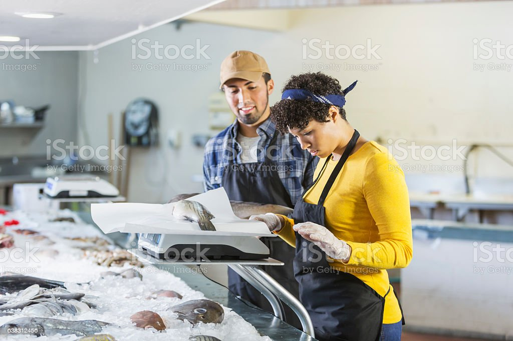 Young mixed race couple working in fish market stock photo