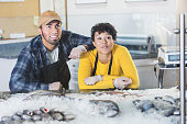 Young mixed race couple working in fish market