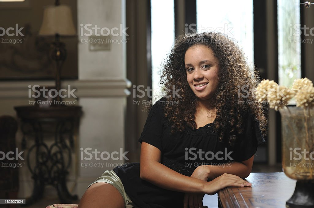 Young mixed race curly hair girl sitting indoors royalty-free stock photo