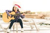 Young mixed race girl playing guitar, singing by swimming pool