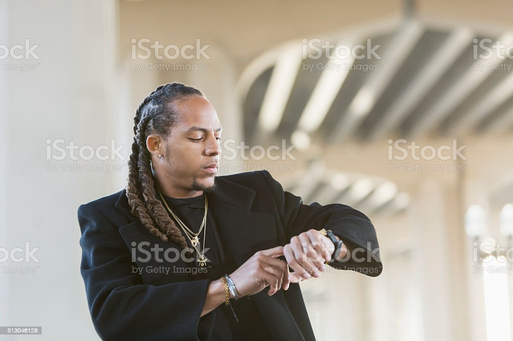 Young mixed race man in black coat looking at watch stock photo