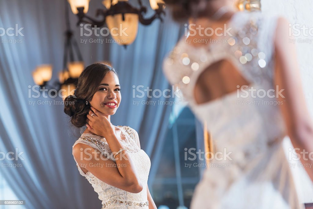 Young mixed race woman in elegant white dress stock photo