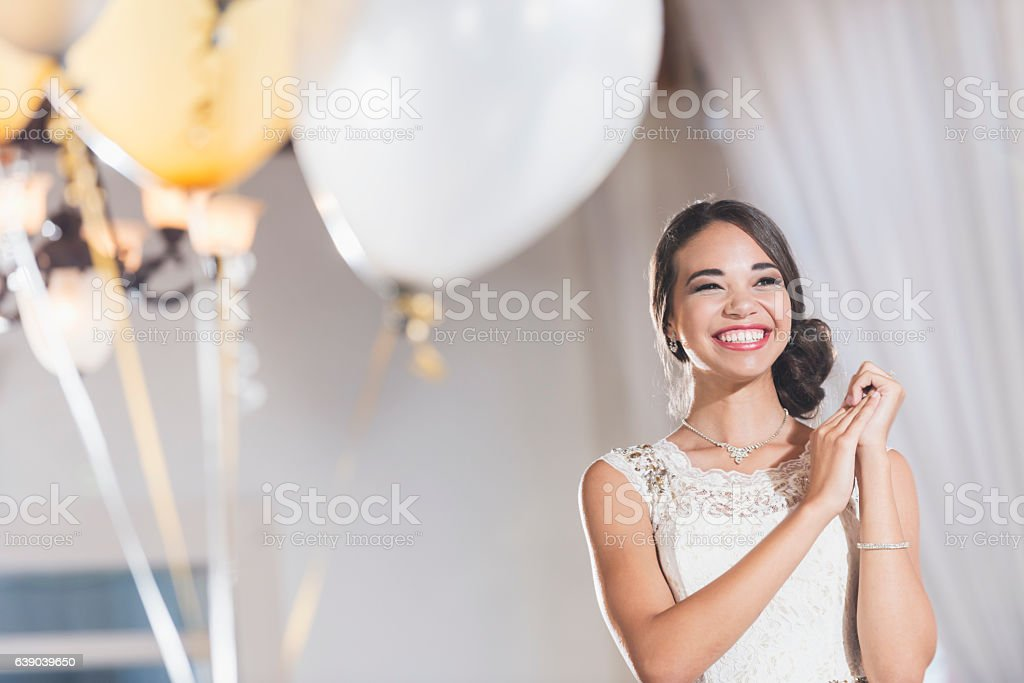 Young mixed race woman in white dress at party stock photo