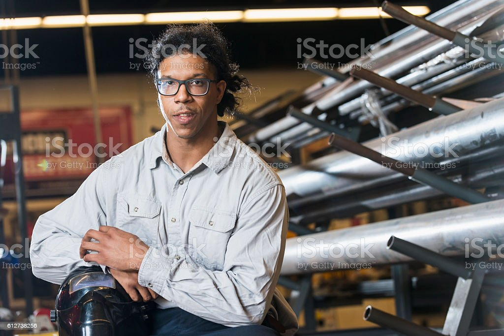 Young mixed race worker holding welders mask stock photo