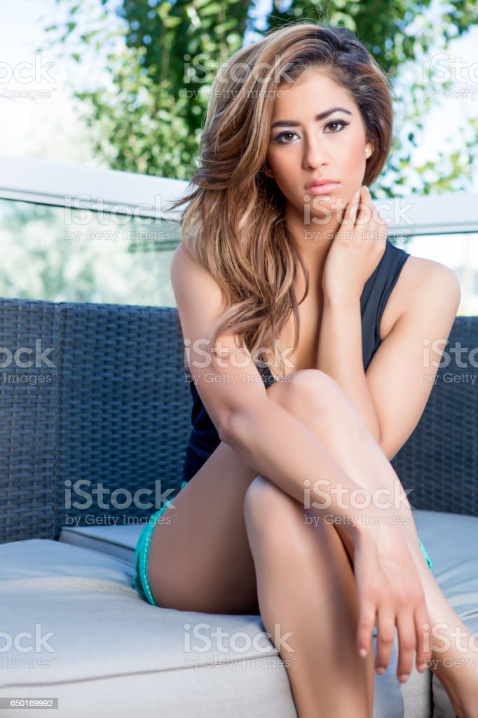Young model sitting on sofa stock photo