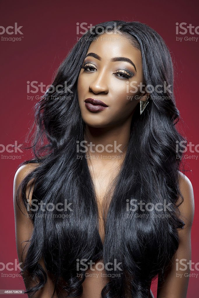 A young model with long black styled hair on red background stock photo