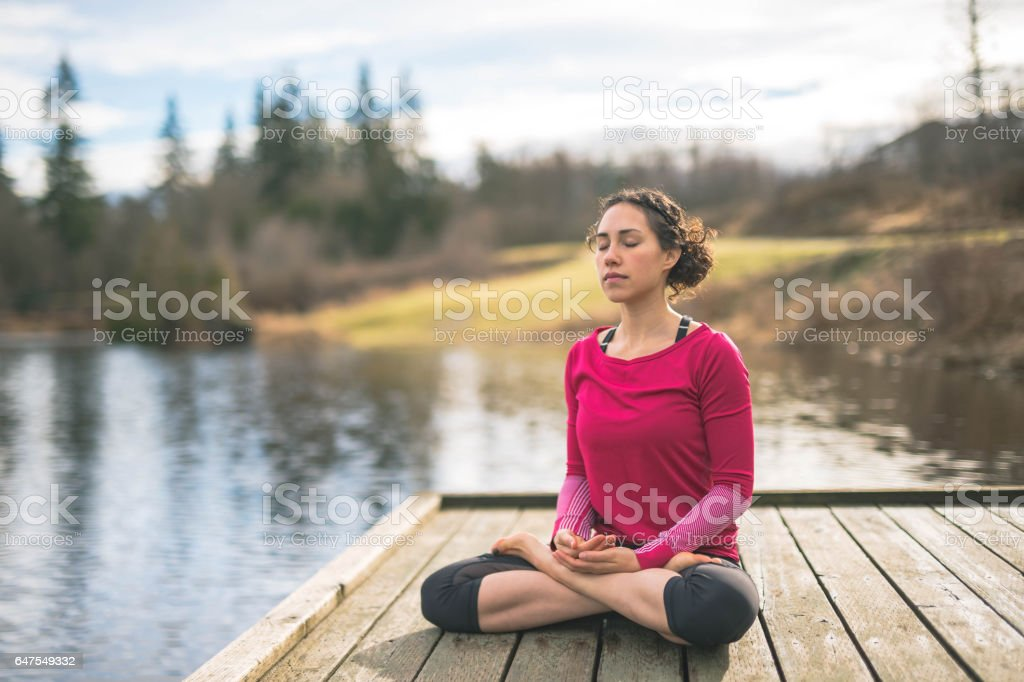 Young mom doing yoga outside by lake stock photo