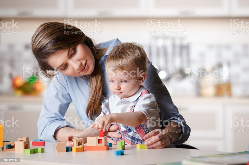 young mom playing with baby stock photo