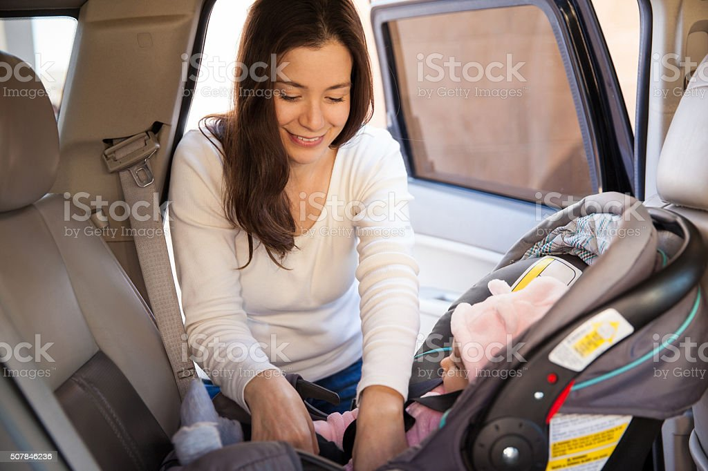 Young mom securing a child car seat stock photo