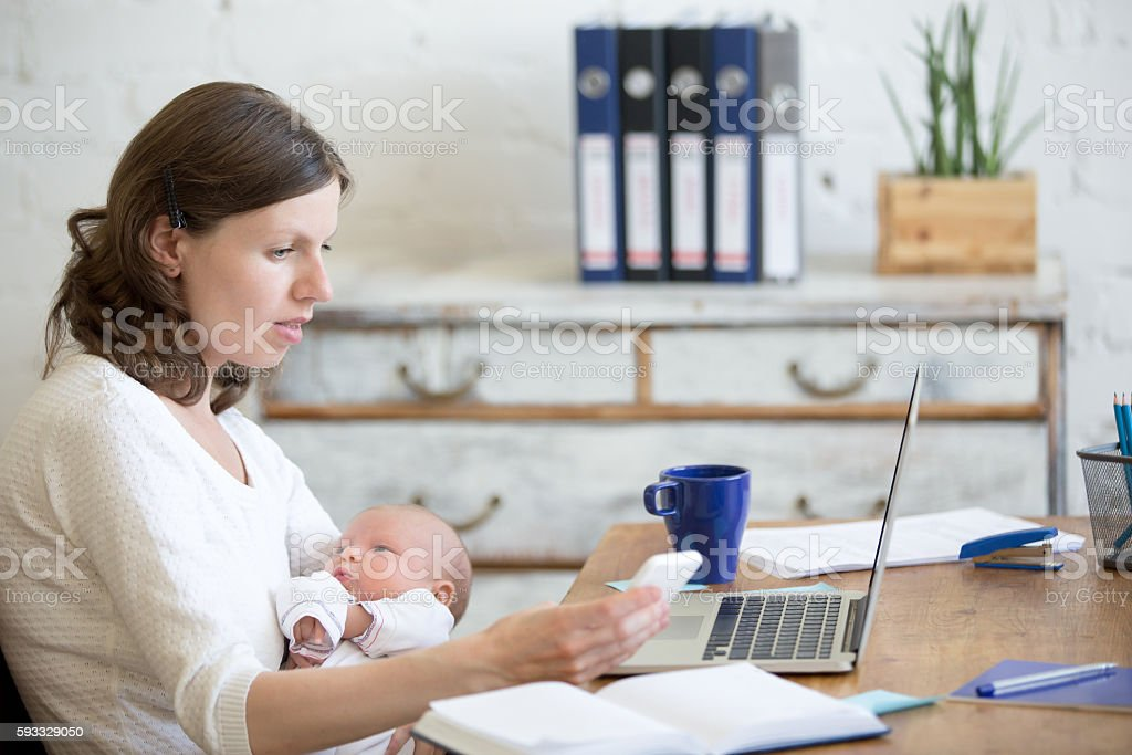 Young mom working and holding child in the office stock photo