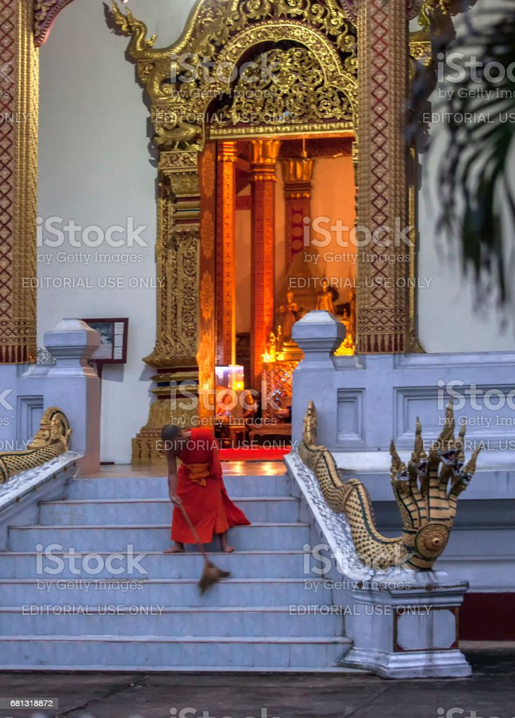Young monk is sweeping the monastery courtyard, Luang Prabang, Laos stock photo