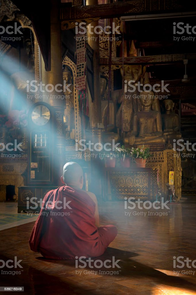 Young Monk Meditating At The Temple Hall stock photo