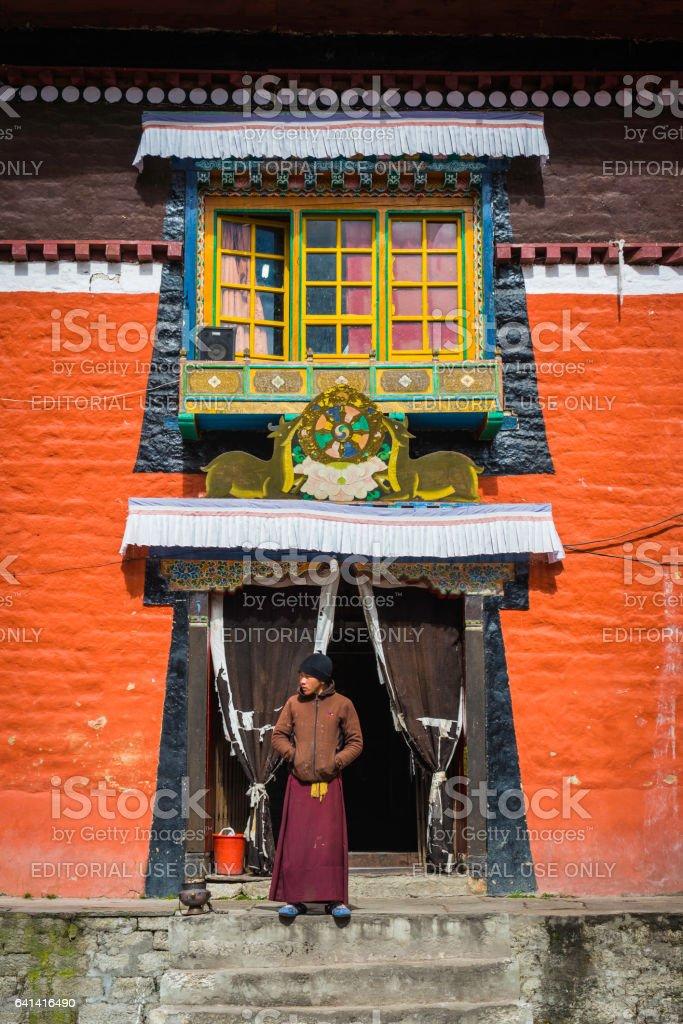 Young monk on steps of Buddhist monastery Khumbu Himalaya Nepal stock photo