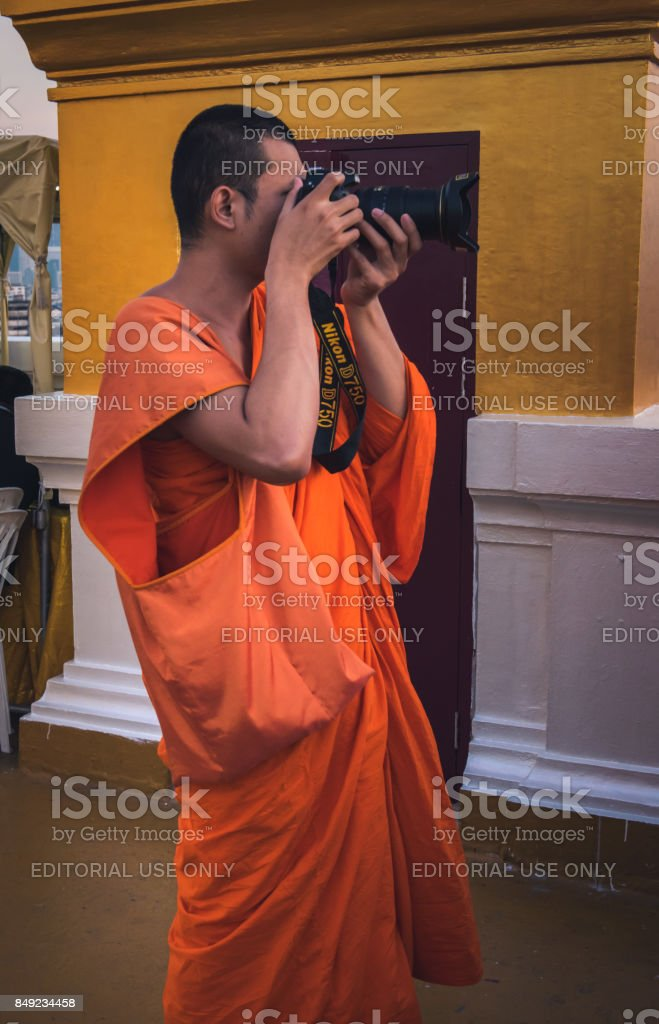 A young monk, taking pictures of the views, from the top of Wat Saket (Golden mountain) stock photo