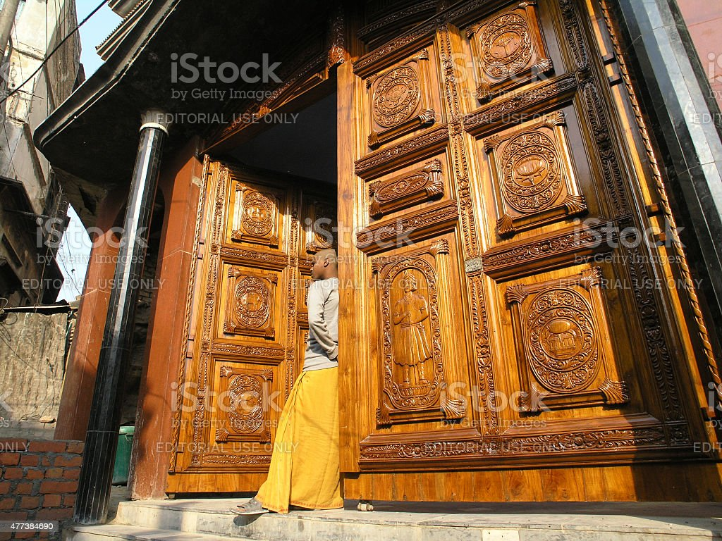 Young monk. Temple entrance. Large wooden doors. stock photo