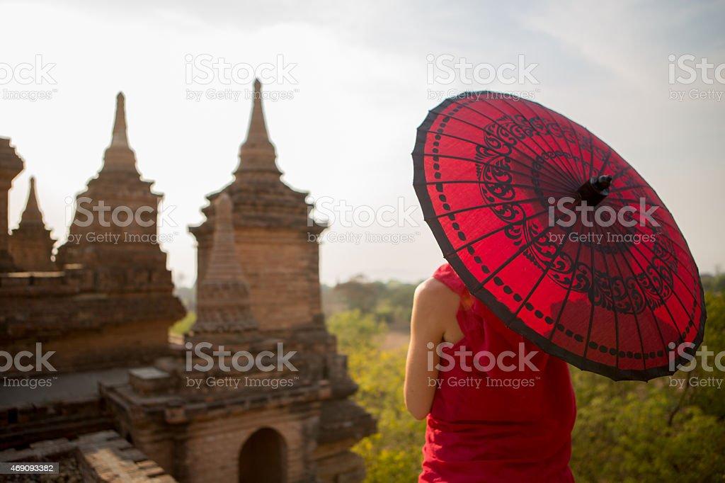 Young Monk with Umbrella Overlooks Bagan Temples, Myanmar. stock photo