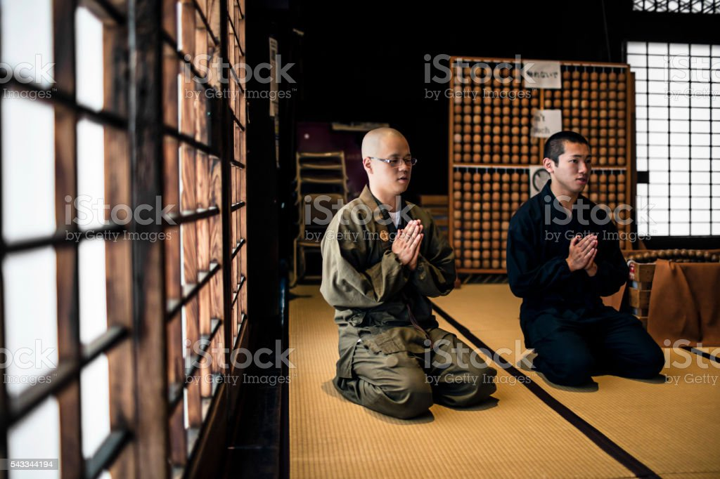 Young monks praying in Buddhist temple stock photo