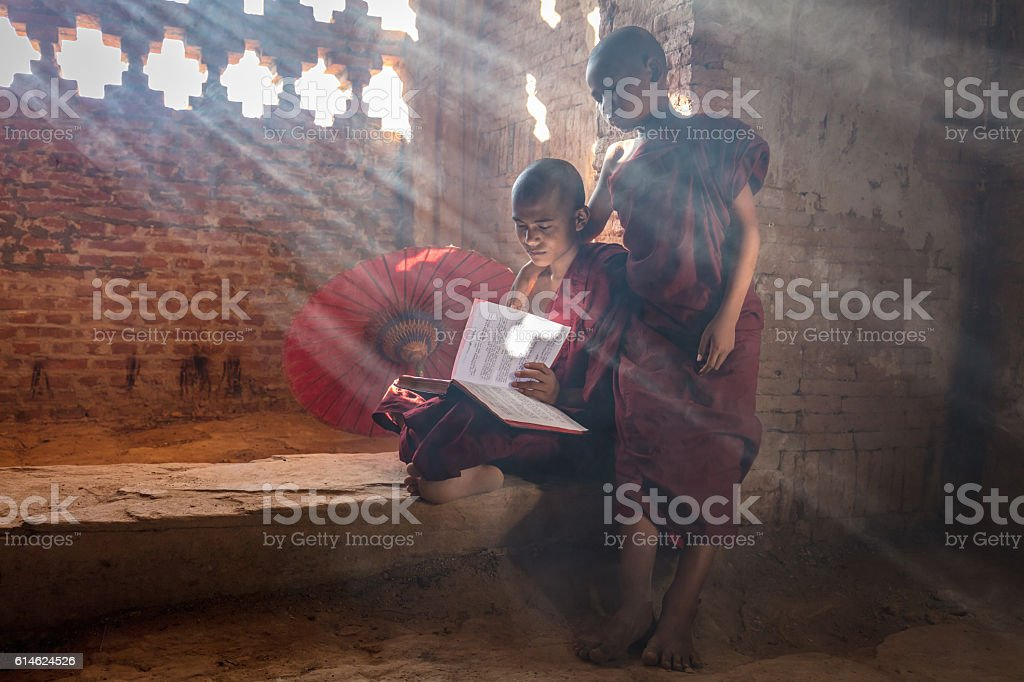 Young Monks reading Buddhist Book inside Temple Bagan Myanmar stock photo