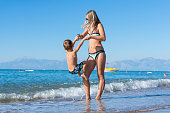 Young mother and baby boy son playing on the beach