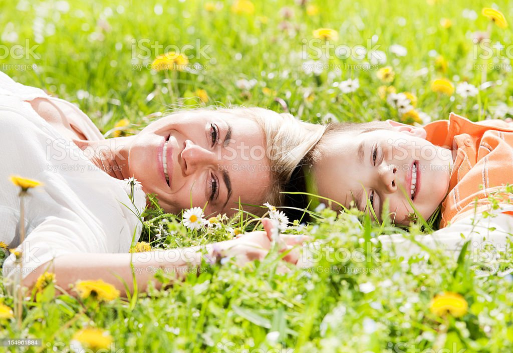 Young mother and child lying on their backs in  field. royalty-free stock photo