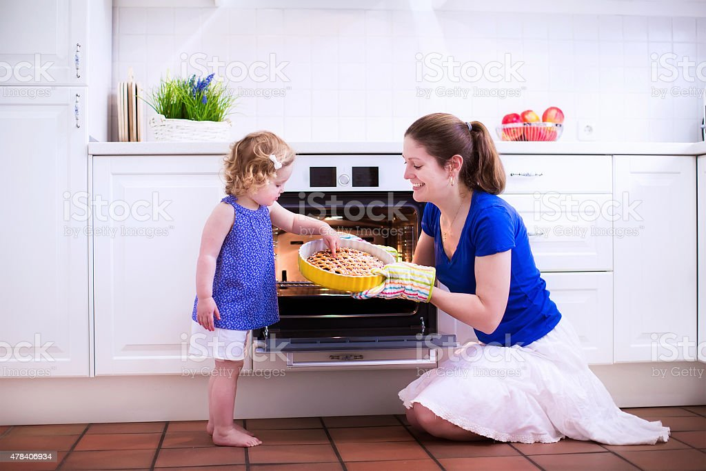 Young mother and cute child baking a cake. stock photo