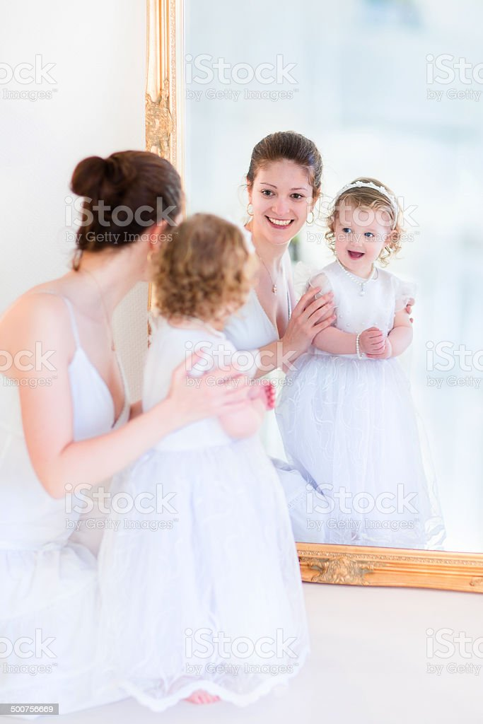Young mother and daughter at a mirror stock photo