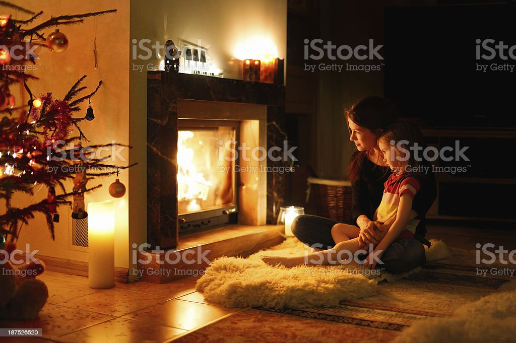 Young mother and daughter by a fireplace stock photo