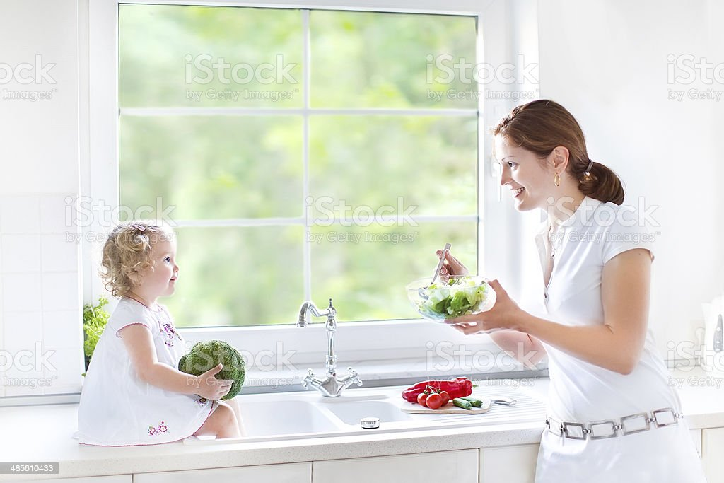 Young mother and daughter cooking salad for lunch in kitchen stock photo