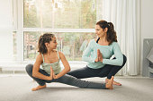 Young mother and daughter doing morning yoga exercise