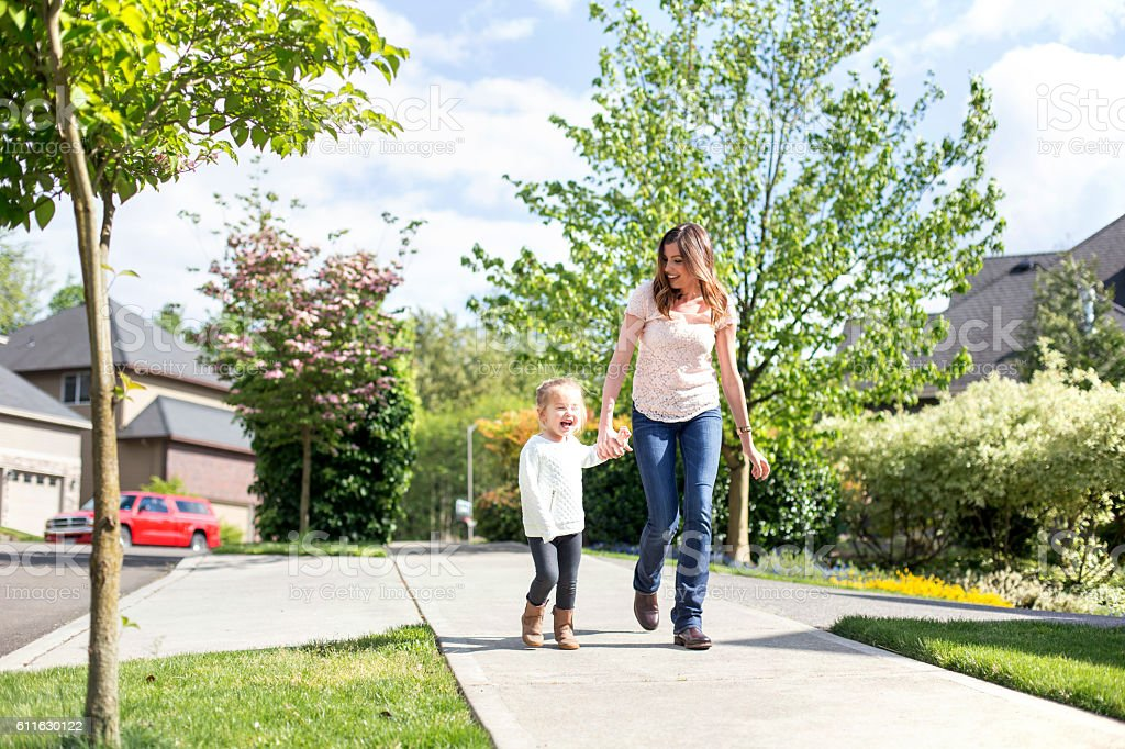 Young mother and daughter laughing as they walk together stock photo