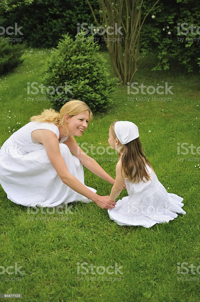 Young mother and daughter playing in garden royalty-free stock photo