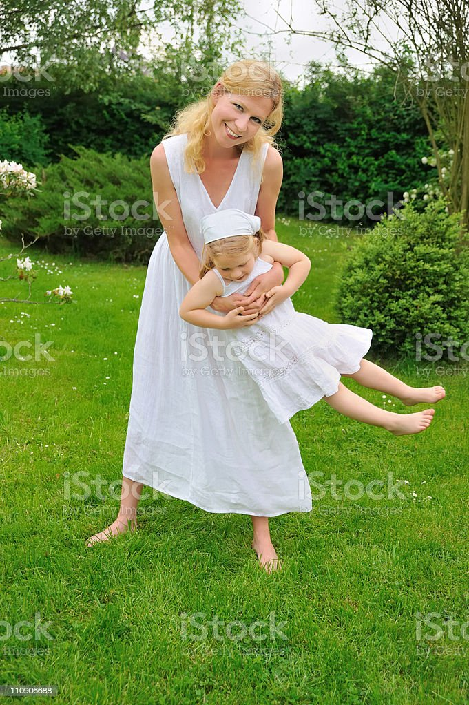 Young mother and daughter playing in meadow royalty-free stock photo
