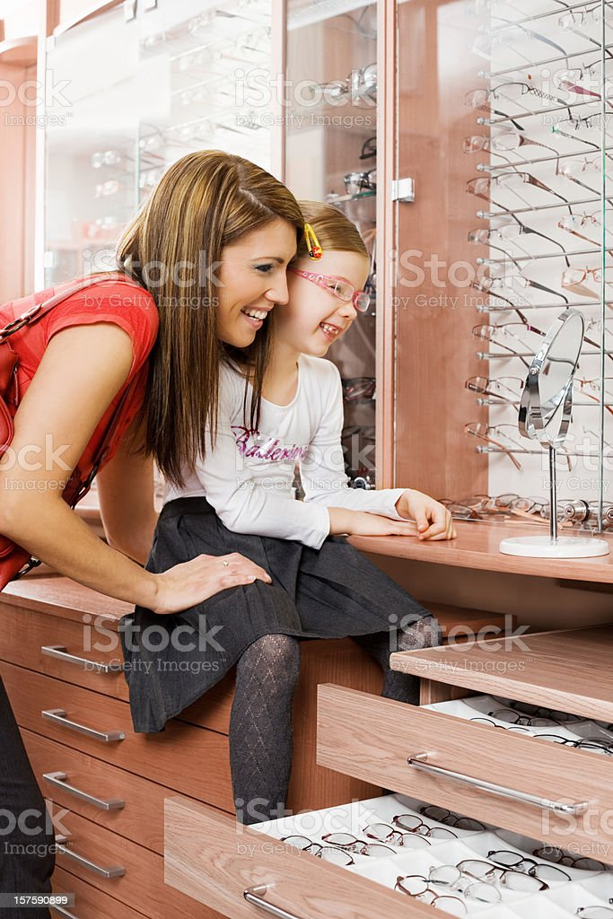 Young Mother And Daughter Shopping For New Glasses royalty-free stock photo