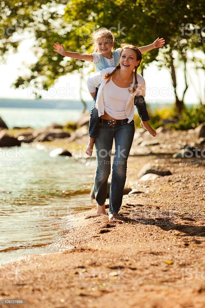 Young Mother and daughter smiling and running on the beach royalty-free stock photo